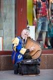 KIEV, UCRÂNIA - 3 DE MAIO DE 2013: O músico da rua na imagem do cossack no traje do nacional joga no gusli Fotografia de Stock