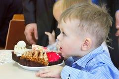 Kiev, Ucrânia - 11 de novembro de 2017: Um rapaz pequeno em uma camisa que come um bolo doce foto de stock