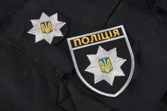 KIEV, UCRÂNIA - 22 DE NOVEMBRO DE 2016 Remendo e crachá da polícia nacional de Ucrânia no fundo uniforme preto imagens de stock