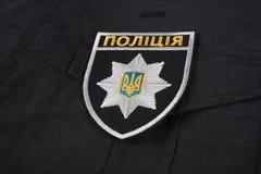 KIEV, UCRÂNIA - 22 DE NOVEMBRO DE 2016 Remendo e crachá da polícia nacional de Ucrânia no fundo uniforme preto fotos de stock royalty free