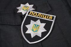 KIEV, UCRÂNIA - 22 DE NOVEMBRO DE 2016 Remendo e crachá da polícia nacional de Ucrânia no fundo uniforme preto imagem de stock royalty free