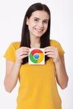 Kiev, Ucraina - 22 agosto 2016: La donna passa giudicare l'icona di Google Chrome stampata su carta su fondo grigio Google è Fotografia Stock Libera da Diritti