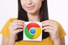 Kiev, Ucraina - 22 agosto 2016: La donna passa giudicare l'icona di Google Chrome stampata su carta su fondo grigio Google è Fotografie Stock Libere da Diritti