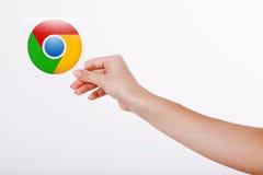 Kiev, Ucraina - 22 agosto 2016: La donna passa giudicare l'icona di Google Chrome stampata su carta su fondo grigio Google è Immagine Stock