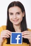 KIEV, UCRAINA - 22 agosto 2016: La donna passa il segno dell'icona del facebook della tenuta stampato su carta su fondo bianco Fa Fotografia Stock Libera da Diritti
