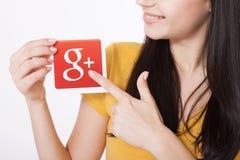 Kiev, Ucraina - 22 agosto 2016: La donna passa la tenuta del Google più l'icona stampata su carta su fondo grigio Google è U.S.A. Immagini Stock Libere da Diritti