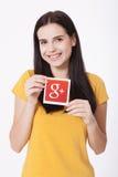 Kiev, Ucraina - 22 agosto 2016: La donna passa la tenuta del Google più l'icona stampata su carta su fondo grigio Google è U.S.A. Immagine Stock Libera da Diritti