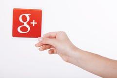 Kiev, Ucraina - 22 agosto 2016: La donna passa la tenuta del Google più l'icona stampata su carta su fondo grigio Google è U.S.A. Fotografia Stock Libera da Diritti