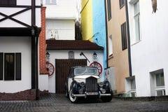 Kiev, Ucraina; 10 aprile 2014 Vecchie automobili sui precedenti di vecchie costruzioni nello stile inglese immagini stock libere da diritti