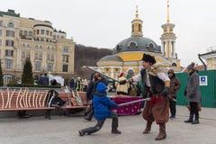 Kiev, Ucraina - 13 gennaio 2018: Torneo divertente sulle sciabole fra un uomo in un costume storico ed i ragazzi Immagine Stock Libera da Diritti