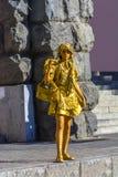 Kiev, Ucraina, il 7 agosto 2018 Ragazza che descrive una statua su una via della città Una statua vivente dipinta in oro fotografie stock