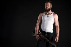 KIEV, UCRAINA - 3 maggio 2017 Un uomo carismatico ed alla moda con una barba giudica una chitarra elettrica in sua mano sul nero  Fotografia Stock Libera da Diritti
