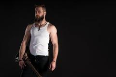 KIEV, UCRAINA - 3 maggio 2017 Un uomo carismatico ed alla moda con una barba giudica una chitarra elettrica in sua mano sul nero  Fotografie Stock Libere da Diritti
