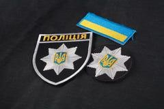 KIEV, UCRAINA - 22 NOVEMBRE 2016 La toppa ed il distintivo della polizia nazionale dell'Ucraina sul nero uniformano il fondo fotografia stock libera da diritti