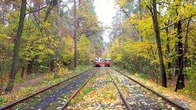 KIEV, UCRAINA - 21 OTTOBRE 2018: Il retro tram rosso nella foresta scenica di autunno della località di soggiorno di clima di Pus stock footage