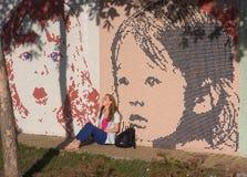 Kiev, Ucraina - 17 settembre 2015: il irl si siede sul catrame alla parete dei graffiti Immagine Stock Libera da Diritti