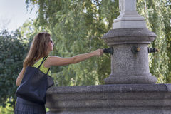 Kiev, Ucraina - 9 settembre 2015: La donna si applica una moneta per buona fortuna al fontana-magnete Immagine Stock Libera da Diritti