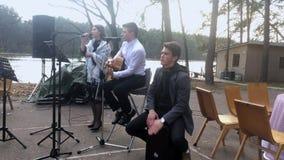 KIEV, UCRANIA - 21 DE ABRIL DE 2019: La banda toca la guitarra, instrumento de percusión y canta una canción en la boda almacen de metraje de vídeo