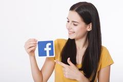 KIEV, UCRANIA - 22 de agosto de 2016: La mujer da llevar a cabo la muestra del icono del facebook impresa en el documento sobre e Fotografía de archivo libre de regalías