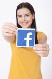 KIEV, UCRANIA - 22 de agosto de 2016: La mujer da llevar a cabo la muestra del icono del facebook impresa en el documento sobre e Imagen de archivo libre de regalías