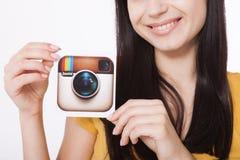 KIEV, UCRANIA - 22 DE AGOSTO DE 2016: La mujer da sostener el papel impreso icono de la cámara del logotipo de Instagram Es un mó Foto de archivo libre de regalías