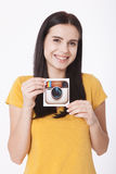 KIEV, UCRANIA - 22 DE AGOSTO DE 2016: La mujer da sostener el papel impreso icono de la cámara del logotipo de Instagram Es un mó Imagen de archivo libre de regalías