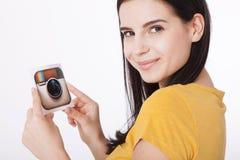 KIEV, UCRANIA - 22 DE AGOSTO DE 2016: La mujer da sostener el papel impreso icono de la cámara del logotipo de Instagram Es un mó Fotografía de archivo