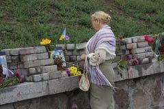 Kiev, Ucrania - 24 de agosto de 2016: Mujer, flores en el monumento de los centenares del cielo de muertos durante la revolución Imagenes de archivo