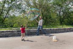 Kiev, Ucrania - 4 de junio de 2016: El artista de la calle sopla burbujas de jabón coloridas enormes Imagen de archivo