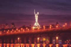 Kiev, Ucrania - 4 de mayo de 2018: Vista del puente de Paton, del monumento de la patria y del río de Dnieper en la noche, paisaj foto de archivo