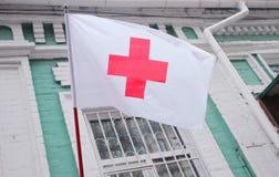 Kiev, Ucrania - 24 de noviembre de 2016: Bandera de la Cruz Roja en el edificio antiguo La organización de la Cruz Roja es una or Fotografía de archivo libre de regalías