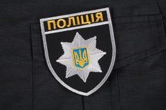 KIEV, UCRANIA - 22 DE NOVIEMBRE DE 2016 El remiendo y la insignia de la policía nacional de Ucrania en negro uniforman el fondo foto de archivo libre de regalías