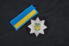 KIEV, UCRANIA - 22 DE NOVIEMBRE DE 2016 El remiendo y la insignia de la policía nacional de Ucrania en negro uniforman el fondo imágenes de archivo libres de regalías