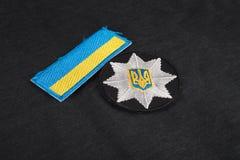 KIEV, UCRANIA - 22 DE NOVIEMBRE DE 2016 El remiendo y la insignia de la policía nacional de Ucrania en negro uniforman el fondo fotografía de archivo