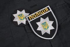 KIEV, UCRANIA - 22 DE NOVIEMBRE DE 2016 El remiendo y la insignia de la policía nacional de Ucrania en negro uniforman el fondo fotos de archivo libres de regalías