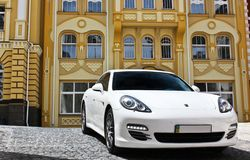 Kiev, Ucrania, el 25 de junio de 2015; Porsche blanco Porsche Panamera en el fondo de edificios hermosos imágenes de archivo libres de regalías