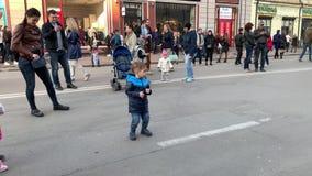 Kiev, Ucrania - marzo de 2019: Día de fiesta en la ciudad Un niño pequeño está bailando en una calle de la ciudad en el primero p metrajes