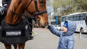 Kiev, Ucrania - 04 14 2019 Polic?a montada Ni?o peque?o con un caballo Una muchedumbre de ucranianos va al estadio a apoyar foto de archivo libre de regalías