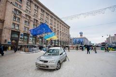 KIEV, UCRANIA: Un coche con nacional y banderas de la UE en la calle vacía de la nieve en el territorio ocupado por los manifestan Imágenes de archivo libres de regalías