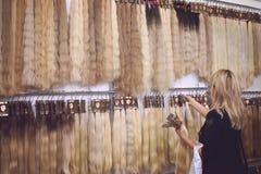 """KIEV UKRAINA †""""19 SEPTEMBER, 2018: Kvinnor väljer Gem-i hårförlängningsutrustning av naturligt hår HårombreBalayage prövkopior royaltyfri bild"""
