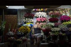 KIEV UKRAINA - AUGUSTI 10, 2015: Åldras kvinna för blomsterhandlare som mitt arbetar på hennes blommor i en tunnelbana av självst Arkivbild