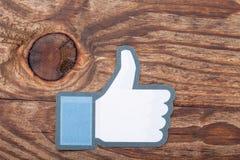 KIEV UKRAINA - AUGUSTI 22, 2015: Facebook tummar upp tecknet utskrivavet papper Är välkänd social nätverkandeservice arkivbilder