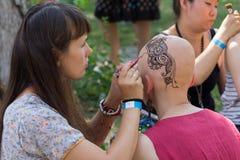 Kiev Ukraina - Augusti 03, 2017: Konstnär som gör en mehenditatuering på huvudet för flicka` s Royaltyfri Foto
