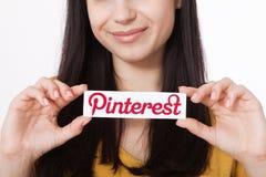 KIEV UKRAINA - AUGUSTI 22, 2016: Kvinnahänder som rymmer Pinterest ilogotype, lurar utskrivavet papper Är fotoet som delar websit Arkivbild
