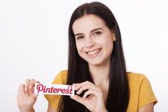 KIEV UKRAINA - AUGUSTI 22, 2016: Kvinnahänder som rymmer Pinterest ilogotype, lurar utskrivavet papper Är fotoet som delar websit Royaltyfri Bild