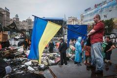 KIEV UKRAINA - AUGUSTI 9, 2014: Man som avfärdar en ukrainsk flagga på Maidan fyrkantbarrikader under deras borttagning royaltyfri fotografi