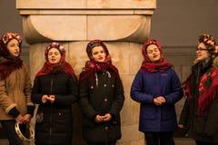 KIEV UKRAINA - 14 JANUARI: Unga flickorna i ukrainska traditionella etniska kläder är sjungande lovsånger på gångtunnelstationen Royaltyfria Foton