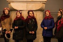 KIEV UKRAINA - 14 JANUARI: Unga flickorna i ukrainska traditionella etniska kläder är sjungande lovsånger på gångtunnelstationen Arkivfoton