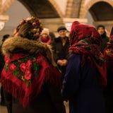 KIEV UKRAINA - 14 JANUARI: Unga flickorna i ukrainska traditionella etniska kläder är sjungande lovsånger på gångtunnelstationen Royaltyfri Fotografi