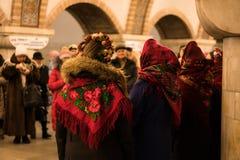 KIEV UKRAINA - 14 JANUARI: Unga flickorna i ukrainska traditionella etniska kläder är sjungande lovsånger på gångtunnelstationen Arkivbild